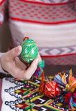 Χρωματισμένα αυγά Πάσχας με τα παραδοσιακά σχέδια στα θηλυκά χέρια Στοκ φωτογραφίες με δικαίωμα ελεύθερης χρήσης