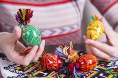Χρωματισμένα αυγά Πάσχας με τα παραδοσιακά σχέδια στα θηλυκά χέρια Στοκ εικόνες με δικαίωμα ελεύθερης χρήσης