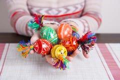 Χρωματισμένα αυγά Πάσχας με τα παραδοσιακά σχέδια στα θηλυκά χέρια Στοκ Εικόνες