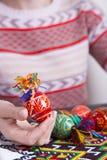 Χρωματισμένα αυγά Πάσχας με τα παραδοσιακά σχέδια στα θηλυκά χέρια Στοκ Φωτογραφίες