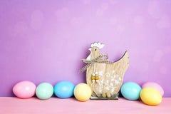 Χρωματισμένα αυγά Πάσχας με τη διακοσμητική κότα στο πορφυρό υπόβαθρο Στοκ Εικόνες