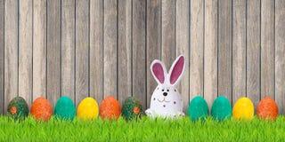 Χρωματισμένα αυγά Πάσχας με το κουνέλι λαγουδάκι στη μέση του ξύλινου υποβάθρου r στοκ εικόνα