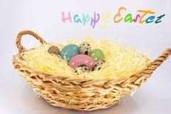 Χρωματισμένα αυγά Πάσχας σε ένα αγροτικό καλάθι και κείμενο σε αγγλικό ευτυχές Πάσχα στοκ εικόνα