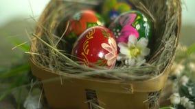 Χρωματισμένα αυγά Πάσχας σε ένα καλάθι με τη χλόη φιλμ μικρού μήκους