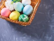 Χρωματισμένα αυγά Πάσχας σε ένα ψάθινο καλάθι Πάσχα, άνοιξη και παραδοσιακές διακοπές Στοκ εικόνα με δικαίωμα ελεύθερης χρήσης