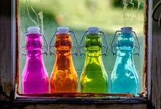 Χρωματισμένα εκλεκτής ποιότητας μπουκάλια στη στρωματοειδή φλέβα παραθύρων Στοκ εικόνα με δικαίωμα ελεύθερης χρήσης