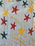 Χρωματισμένα ζωηρόχρωμα αστέρια στο ύφασμα λινού Στοκ Εικόνες