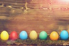 Χρωματισμένα ζωηρόχρωμα αυγά Πάσχας με το πράσινο βρύο στο ξύλινο υπόβαθρο Στοκ Εικόνες