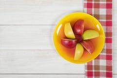 Χρωματισμένα διαιρεμένα στα τέσσερα μήλα που τοποθετούνται σε ένα πιατάκι Στοκ Εικόνες