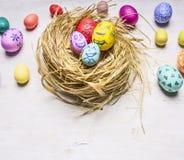 Χρωματισμένα διακοσμητικά αυγά για Πάσχα, στη θέση συνόρων φωλιών για το ξύλινο αγροτικό υπόβαθρο κειμένων κοντά επάνω Στοκ φωτογραφία με δικαίωμα ελεύθερης χρήσης
