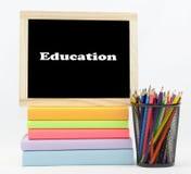 Χρωματισμένα κείμενο βιβλία εκπαίδευσης με τα χρωματισμένα μολύβια Στοκ φωτογραφία με δικαίωμα ελεύθερης χρήσης