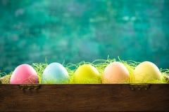 Χρωματισμένα κρητιδογραφία αυγά Πάσχας στην ξύλινη κάρτα κιβωτίων, Πάσχας ή ανοίξεων Στοκ Εικόνες