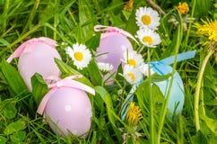 Χρωματισμένα κρητιδογραφία αυγά Πάσχας μεταξύ των λουλουδιών Στοκ Φωτογραφία