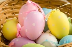 Χρωματισμένα κρητιδογραφία αυγά Πάσχας σε ένα καλάθι αχύρου Στοκ Εικόνες