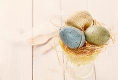 Χρωματισμένα κρητιδογραφία αυγά Πάσχας στο καλάθι αχύρου Στοκ φωτογραφίες με δικαίωμα ελεύθερης χρήσης