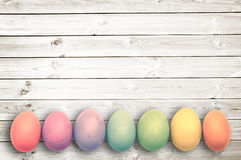 Χρωματισμένα κρητιδογραφία αυγά στις άσπρες ξύλινες σανίδες, έννοια Πάσχας Στοκ Φωτογραφίες