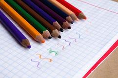 Χρωματισμένα μολύβια με τα χρωματισμένα λωρίδες έπειτα Πολύχρωμα λωρίδες Χρωματισμένα μολύβια για τα παιδιά Σχεδιασμός με τα παιδ στοκ φωτογραφία