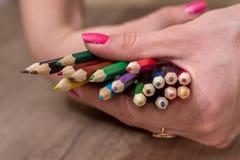 Χρωματισμένα μολύβια που τίθενται στο χέρι γυναικών Στοκ φωτογραφία με δικαίωμα ελεύθερης χρήσης