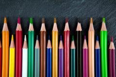 Χρωματισμένα μολύβια σε μια μαύρη πλάκα πετρών Στοκ Εικόνες