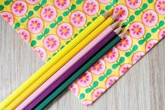 Χρωματισμένα μολύβια στο floral υπόβαθρο Στοκ φωτογραφία με δικαίωμα ελεύθερης χρήσης
