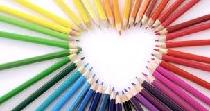 Χρωματισμένα μολύβια που τακτοποιούνται στη μορφή καρδιών στο άσπρο υπόβαθρο απόθεμα βίντεο