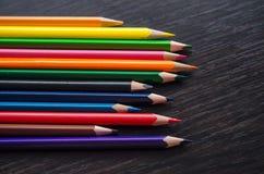 Χρωματισμένα μολύβια στο σκοτεινό υπόβαθρο στοκ εικόνα