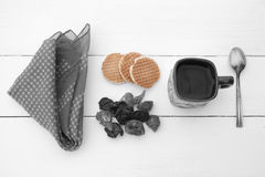 Χρωματισμένα μπισκότα, μαύρο άσπρο φλυτζάνι με το ζεστό νερό και χαρτομάνδηλο Στοκ Φωτογραφία