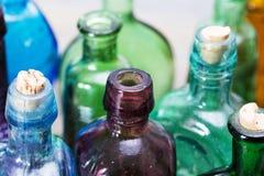 Χρωματισμένα μπουκάλια γυαλιού σε ένα αγροτικό υπόβαθρο Στοκ φωτογραφίες με δικαίωμα ελεύθερης χρήσης