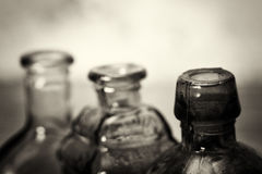 Χρωματισμένα μπουκάλια γυαλιού σε ένα αγροτικό υπόβαθρο Στοκ Φωτογραφία