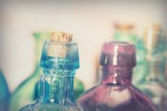 Χρωματισμένα μπουκάλια γυαλιού σε ένα αγροτικό υπόβαθρο Στοκ εικόνα με δικαίωμα ελεύθερης χρήσης