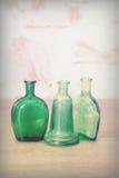 Χρωματισμένα μπουκάλια γυαλιού σε ένα αγροτικό υπόβαθρο Στοκ φωτογραφία με δικαίωμα ελεύθερης χρήσης