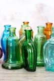 Χρωματισμένα μπουκάλια γυαλιού σε ένα αγροτικό υπόβαθρο Στοκ Φωτογραφίες