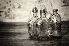 Χρωματισμένα μπουκάλια γυαλιού σε ένα αγροτικό υπόβαθρο Στοκ εικόνες με δικαίωμα ελεύθερης χρήσης