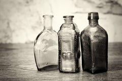 Χρωματισμένα μπουκάλια γυαλιού σε ένα αγροτικό υπόβαθρο Στοκ Εικόνα
