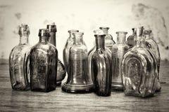 Χρωματισμένα μπουκάλια γυαλιού σε ένα αγροτικό υπόβαθρο Στοκ Εικόνες