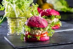 Χρωματισμένα πορφυρά κουλούρια παντζαριών και burgers κοτόπουλου Στοκ εικόνα με δικαίωμα ελεύθερης χρήσης
