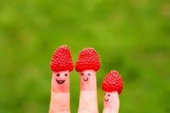 Χρωματισμένα πρόσωπα στα δάχτυλα με τα καπέλα σμέουρων Στοκ Εικόνες