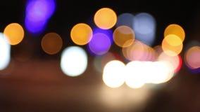 Χρωματισμένα φω'τα της κίνησης των αυτοκινήτων στη σκοτεινή πόλη νύχτας από την εστίαση απόθεμα βίντεο