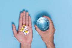 Χρωματισμένα χάπια υπό εξέταση με το νερό στο μπλε υπόβαθρο Στοκ φωτογραφία με δικαίωμα ελεύθερης χρήσης