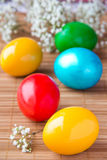 Χρωματισμένα χρωματισμένα αυγά στον πίνακα μπαμπού Στοκ Φωτογραφία