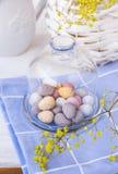 Χρωματισμένα speckled αυγά Πάσχας σοκολάτας στο βάζο κουδουνιών κρυστάλλου στην μπλε πετσέτα στον άσπρο πίνακα, καλάθι με τα κίτρ Στοκ Εικόνες