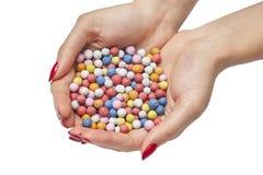 Χρωματισμένες καραμέλες στα θηλυκά χέρια Στοκ Φωτογραφία