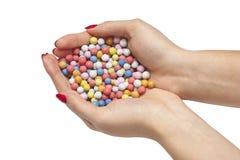 Χρωματισμένες καραμέλες στα θηλυκά χέρια Στοκ Εικόνες