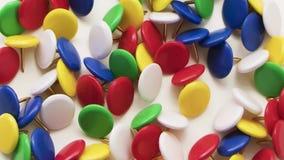 Χρωματισμένες καρφίτσες ώθησης σε ένα άσπρο υπόβαθρο απόθεμα βίντεο