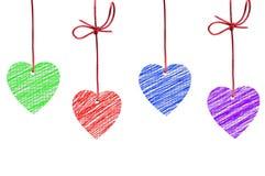 Χρωματισμένες καρδιές που κρεμούν στο λευκό Στοκ φωτογραφίες με δικαίωμα ελεύθερης χρήσης
