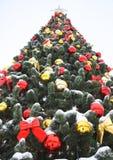 Χρωματισμένες σφαίρες και κόκκινα τόξα στο χριστουγεννιάτικο δέντρο στοκ εικόνες