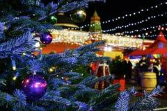 Χρωματισμένες σφαίρες στο χριστουγεννιάτικο δέντρο υπαίθριο Υπόβαθρο φωτισμού με τους γιορτάζοντας ανθρώπους Διάθεση διακοπών στοκ φωτογραφία με δικαίωμα ελεύθερης χρήσης