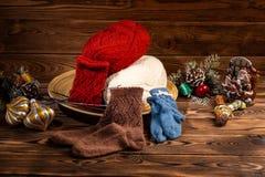 Χρωματισμένες σφαίρες του νήματος, των πολύχρωμων πλεκτών καλτσών και των διακοσμήσεων χριστουγεννιάτικων δέντρων στο ξύλινο υπόβ στοκ φωτογραφία
