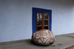 Χρωματισμένη βιοτεχνία γάτα πετρών πέρα από ένα κιγκλίδωμα Στοκ φωτογραφία με δικαίωμα ελεύθερης χρήσης