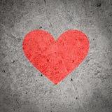Χρωματισμένη κόκκινη καρδιά στο σκοτεινό γκρίζο συμπαγή τοίχο, κατασκευασμένο υπόβαθρο Στοκ Φωτογραφίες